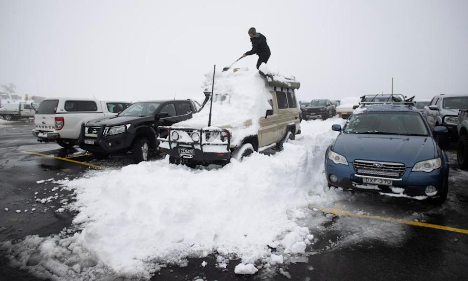 Matthew, a Queenslander from Brisbane on his first visit to the Australian Alps digs out his car staring at the roof