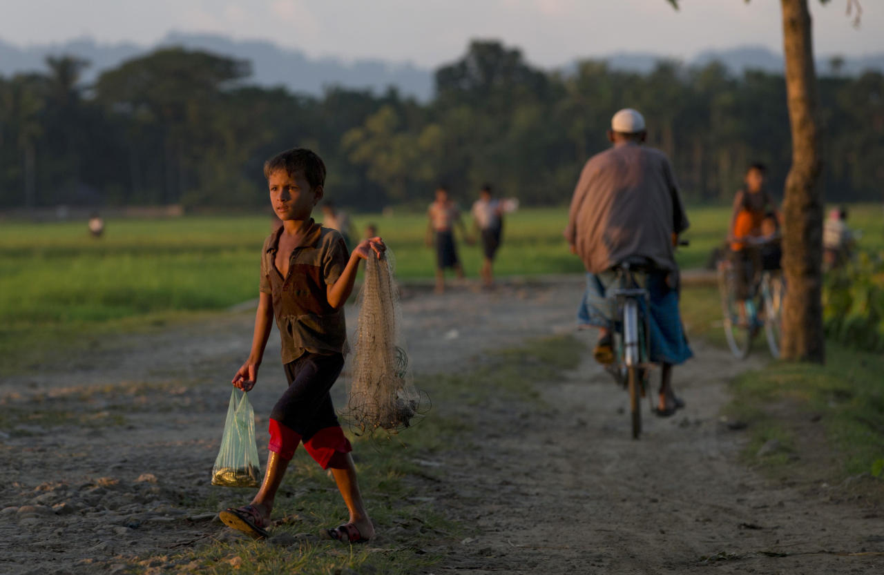 In this Sept. 12, 2013 photo, a Muslim child walks with a net and some fish in a bag close to Myinn Hlut village, Maungdaw, Rakhine state, Myanmar. Children are the biggest victims of policies that for decades have systematically discriminated against Rohingya Muslims. With little or no food security, poverty-stricken families often put kids to work instead of sending them to school. (AP Photo/Gemunu Amarasinghe)