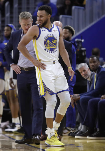Golden State Warriors coach Steve Kerr, left, observes Stephen Curry (30) after Phoenix Suns' Aron Baynes fell onto him during the second half of an NBA basketball game Wednesday, Oct. 30, 2019, in San Francisco. Curry left the game. (AP Photo/Ben Margot)