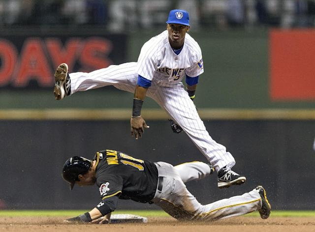 Milwaukee Brewers' Jean Segura, top, gets the force-out on Pittsburgh Pirates' Neil Walker while turning a double play during the first inning of a baseball game on Friday, April 11, 2014, in Milwaukee. (AP Photo/Tom Lynn)