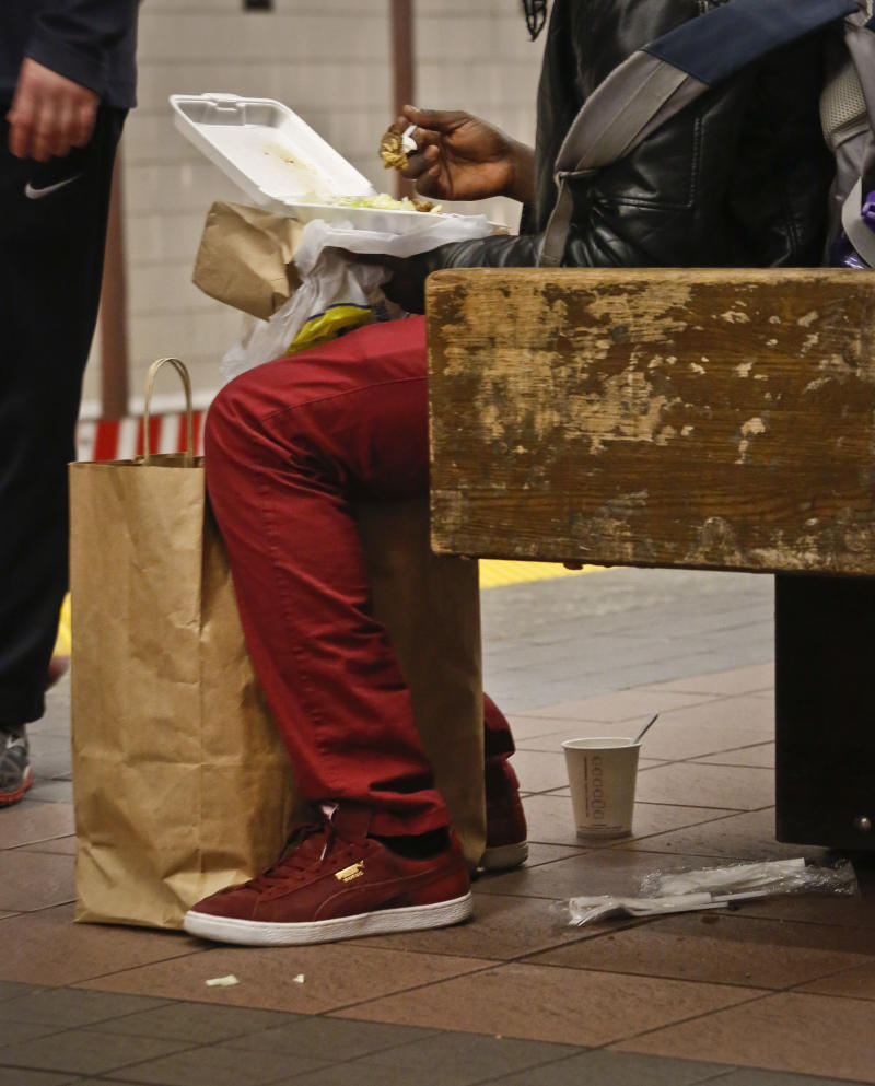 A subway commuter eats next to litter, Thursday March 30, 2017, in New York.  Faced with the problem of too much litter and too many rats in their subway stations, New York City transit officials began an unusual social experiment a few years ago. They removed trash bins entirely from select stations, figuring it would deter people from bringing garbage into the subway in the first place. This week, they pulled the plug on the program after reluctantly concluding that it was a failure.  (AP Photo/Bebeto Matthews)
