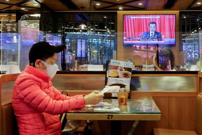 A TV screen showing news over the opening session of the National People's Congress (NPC), is seen in Hong Kong
