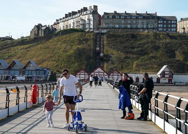 People enjoy the warm weather on the pier at Saltburn-by-the-Sea, North Yorkshire