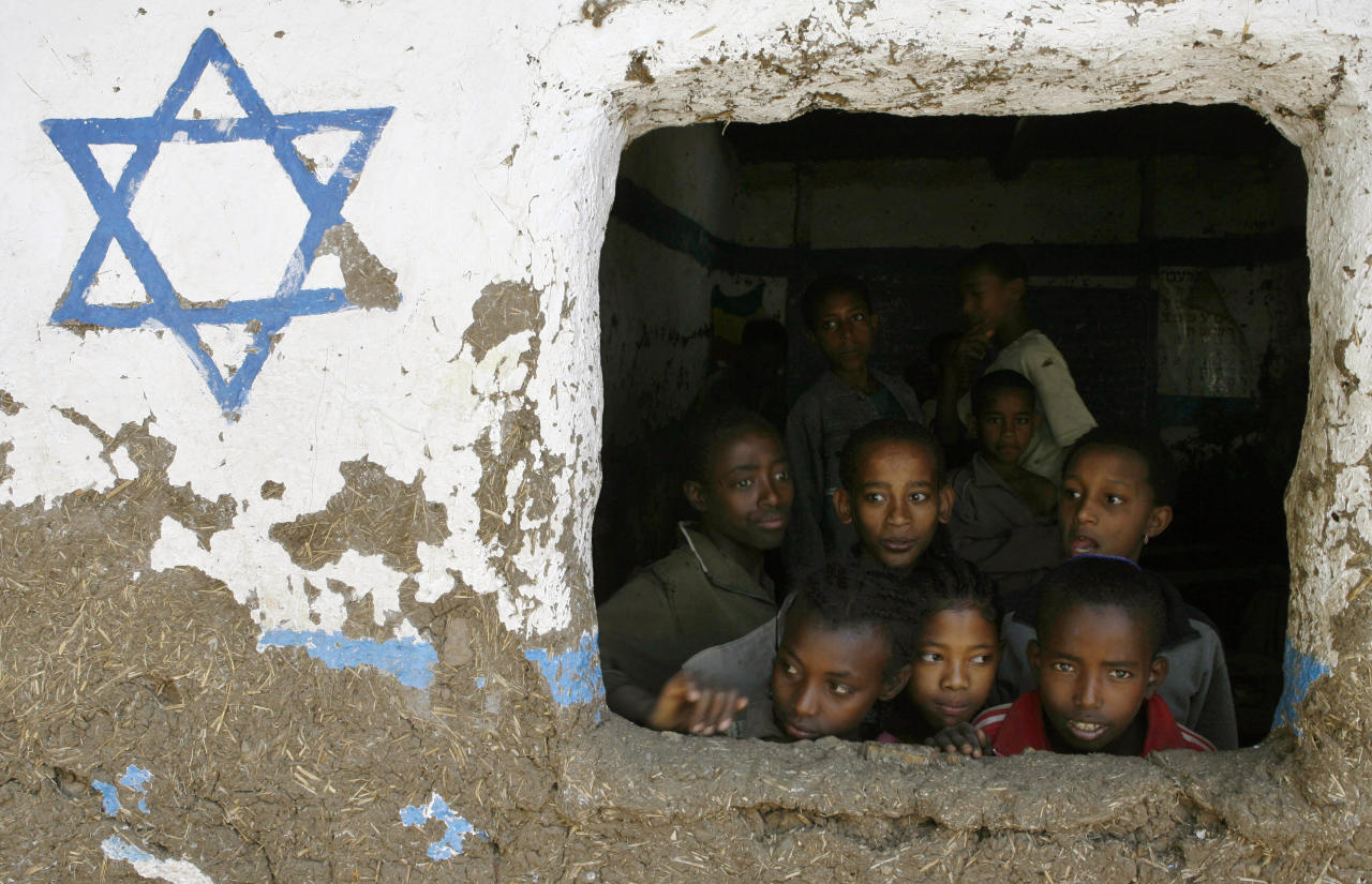 Ethiopian children, whose roots trace back to Judaism, look out of a window at Beta Israel school while awaiting immigration to Israel, in Gondar March 8, 2007. More than 5000 Ethiopians are waiting to migrate to Israel to reunite with their families, according to Israel's Jewish Agency.  REUTERS/Eliana Aponte (ETHIOPIA)