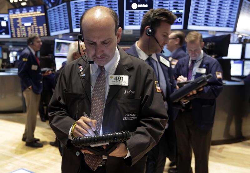Trader Andrew Silverman, foreground left, works on the floor of the New York Stock Exchange, Tuesday, Nov. 19, 2013. Stocks are lower in early trading on Wall Street as traders pick over some disappointing corporate earnings. (AP Photo/Richard Drew)