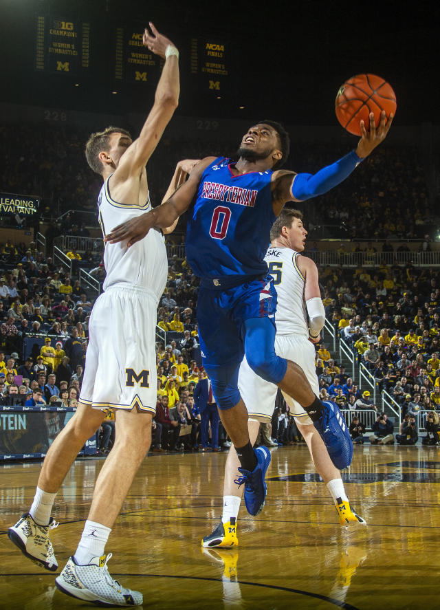 Presbyterian guard Chris Martin (0) shoots as Michigan guard Franz Wagner, left, defends in the first half of an NCAA college basketball game at Crisler Center in Ann Arbor, Mich., Saturday, Dec. 21, 2019. (AP Photo/Tony Ding)