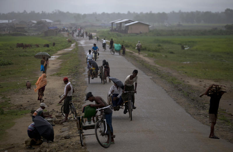In this Sept. 17, 2013 photo, Muslim people, who become displaced following the 2012 sectarian violence, travel close to Bawda Pa IDP camp in Rakhine state, Myanmar. President Thein Sein traveled to Myanmar's conflict-torn west on Tuesday, Oct. 1, 2013 as a new spate of sectarian violence gripped the state of Rakhine, with police saying Buddhist rioters killed a 94-year-old Muslim woman and torched more than 70 homes. (AP Photo/Gemunu Amarasinghe)