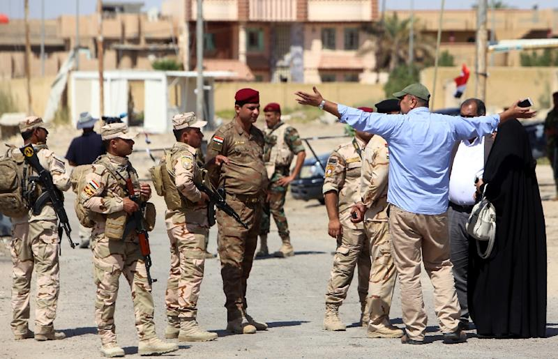 Iraqi security forces escort families returing to their homes in the city of Fallujah after Iraqi forces retook the city back from the Islamic State jihadists (AFP Photo/Sabah Arar)