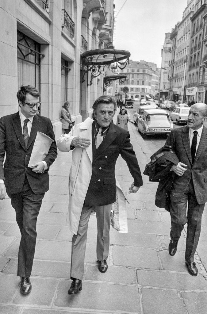 <p>Kirk Douglas appears to be in a hurry as he walks down the street in Paris with French filmmaker Bertrand Tavernier.</p>