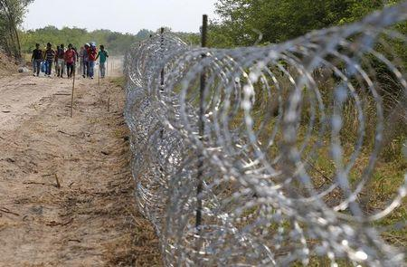 Migrants walk by a fence on the Hungarian-Serbian border near Asotthalom