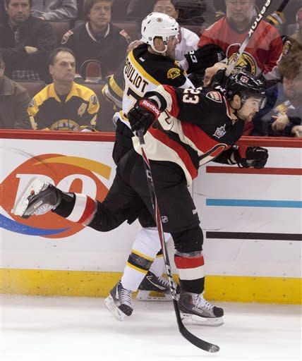 Ottawa Senators left wing Kaspars Daugavins collides with Boston Bruins left wing Benoit Pouliot along the boards during first-period NHL hockey game action in Ottawa on Wednesday, Dec. 14, 2011. (AP Photo/The Canadian Press, Adrian Wyld)