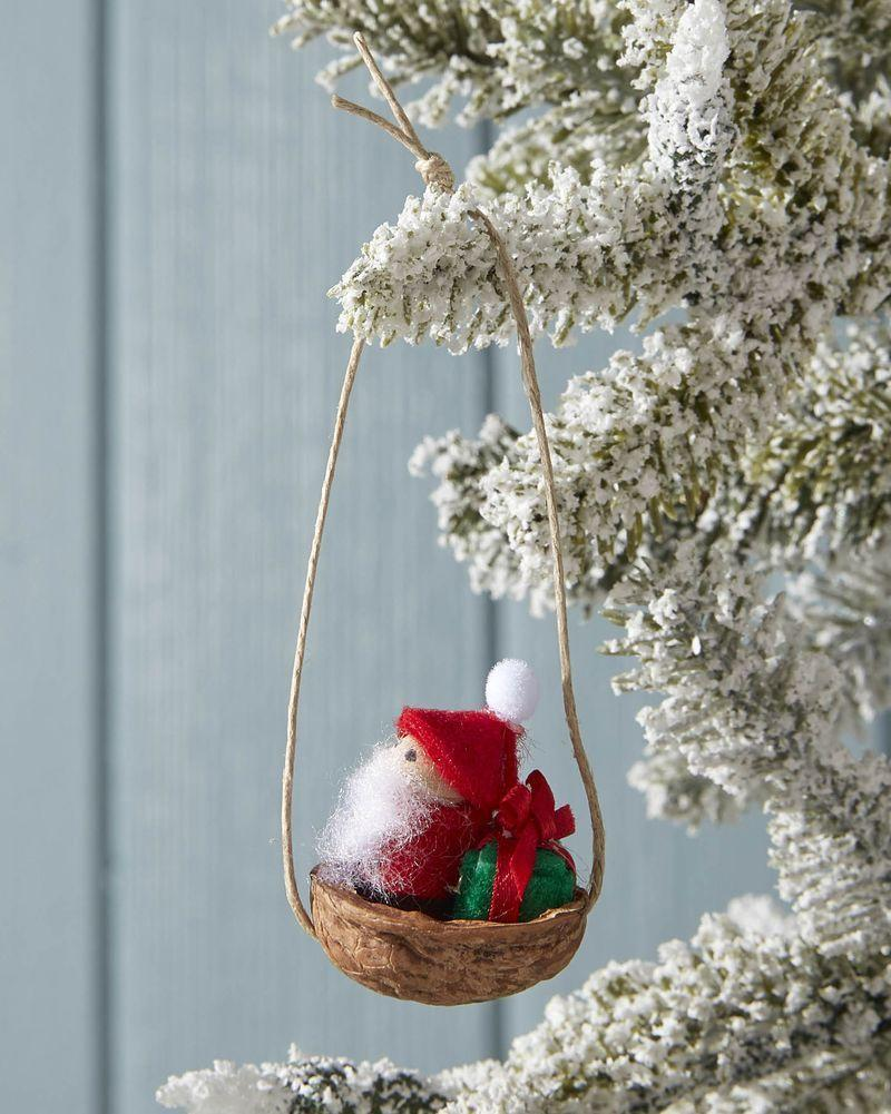 """<p>Santa will delight all who spy him on the tree in his mini walnut shell sleigh.</p><p><strong>To make:</strong> Draw eyes on the face of a small wooden peg doll with a fine-tip black marker. Wrap the body of the doll in red felt, holding it in place with hot glue. Create a small hat from red felt, gluing it to the doll's head with hot glue. Attach a mini pom pom to the hat. Cover a mini wooden cube in green felt, holding it in place with hold glue. Tie a ribbon around the present. Drill small holes on either end of half of a walnut shell. Thread a piece of thin twine through each hole, securing it on the inside of the shell with hot glue. Knot the twine at the top for hanging. Use hot glue to secure Santa and the present in the shell.</p><p><a class=""""link rapid-noclick-resp"""" href=""""https://www.amazon.com/dp/B00WQDTTCE?tag=syn-yahoo-20&ascsubtag=%5Bartid%7C10050.g.1070%5Bsrc%7Cyahoo-us"""" rel=""""nofollow noopener"""" target=""""_blank"""" data-ylk=""""slk:SHOP MINI WOODEN PEG DOLLS"""">SHOP MINI WOODEN PEG DOLLS</a></p>"""