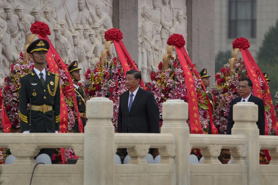 Chinese President Xi Jinping, center, with Premier Li Keqiang, right, walks past wreaths of flowers and a member of an honor guard after he paid respects to the Monument to the People's Heroes during a ceremony to mark Martyr's Day at Tiananmen Square in Beijing, Thursday, Sept. 30, 2021. (AP Photo/Andy Wong)