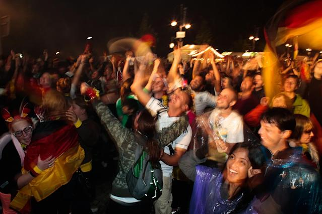 In this picture taken with a long shutter, German fans celebrate their team after Germany won against Argentina by 1-0 at the soccer World Cup final in Rio de Janeiro, Brazil, at a public viewing area called 'Fan Mile' in Berlin, Sunday, July 13, 2014. (AP Photo/Markus Schreiber)