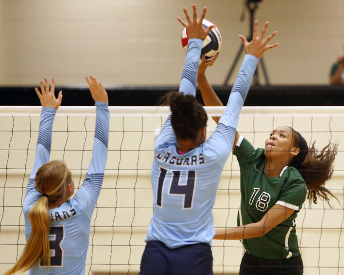 "FILE - Reagan's Kyla Waiters, right, spikes the ball past Johnson defenders during a Texas District 26-6A high school volleyball match in San Antonio, Texas, in this Friday, Sept. 22, 2017, file photo. Oregon State leaders are suing to block disclosure of details about an investigation of abuse allegations in their volleyball program, even as they tout a refreshed mission for transparency in wake of their president's resignation over the handling of sexual-misconduct cases at another school. ""I'm guessing there's something in those records that they don't want out,"" said Dorina Waiters, whose daughter, Kyla, left Oregon State after a year on the volleyball team triggered depression that led to suicidal thoughts. (Ron Cortes/The San Antonio Express-News via AP, File)"