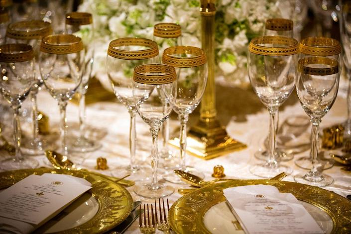 """<p>For the china, Melania chose a gold set <a rel=""""nofollow noopener"""" href=""""https://www.nytimes.com/2018/04/25/fashion/state-dinner-melania-trump-brigitte-macron.html"""" target=""""_blank"""" data-ylk=""""slk:from the Clinton White House"""" class=""""link rapid-noclick-resp"""">from the Clinton White House</a>, which created a regal, yet sophisticated ambiance.</p>"""
