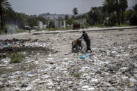 A woman pushes a wheelchair, carrying her empty water containers, through an empty street littered with trash near the judiciary and legislative buildings, in Port-au-Prince, Haiti, Tuesday, Sept. 22, 2021. Most of the population of Port-au-Prince has no access to basic public services, no drinking water, electricity or garbage collection. (AP Photo/Rodrigo Abd)