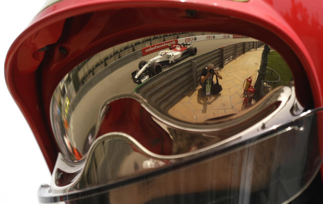 Sauber driver Charles Leclerc of Monaco steering his car is seen reflected in a security officer's helmet during a practice session in Monaco, Thursday, May 24, 2018. The Formula one race will be held on Sunday. (AP Photo/Luca Bruno)