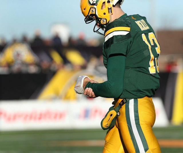 Edmonton QB Mike Reilly holds his wrist while walking off the field during the second half of CFL eastern semifinal against Tiger Cats, in Hamilton. (THE CANADIAN PRESS/Peter Power photo)