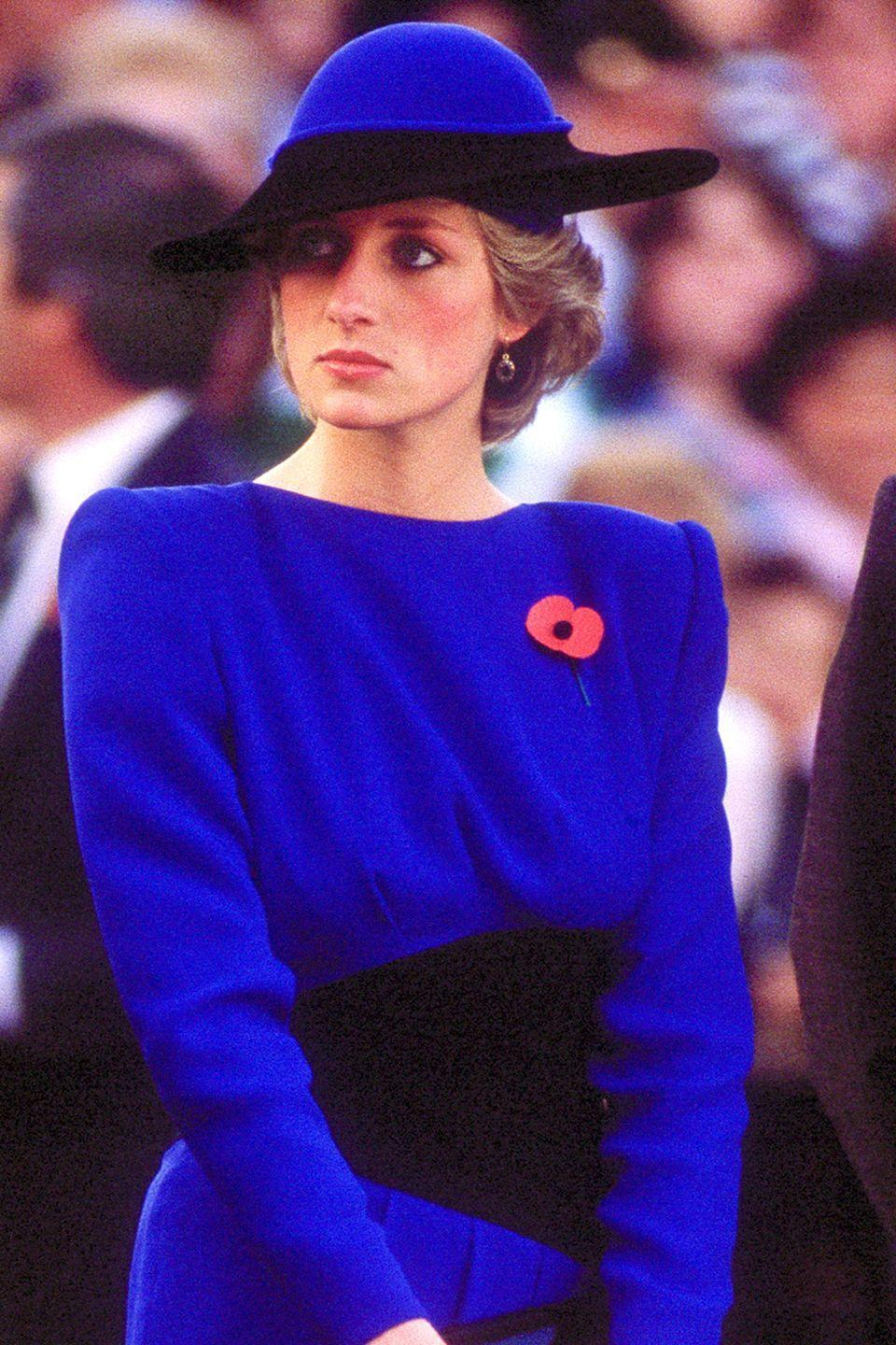 <p>In a blue-and-black color-block Bruce Oldfield hat. </p>