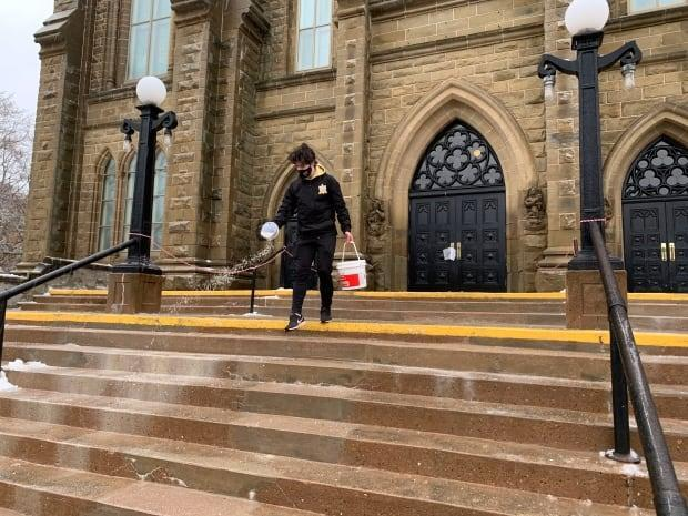 Isaac Bourque scatters salt on the steps at St. Dunstan's Basilica in Charlottetown Sunday morning. The icy weather didn't stop the Easter service. (Shane Ross/CBC - image credit)