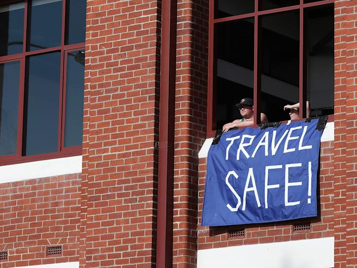 "Residents in apartments opposite the Fremantle Passenger Terminal are seen with a banner with a message to the passengers and crew of the MV Artania saying ""Travel Safe"" on March 28, 2020."