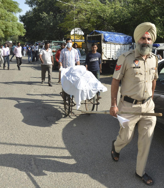 The body of a victim of Friday's train accident is carried away in a cart outside a hospital in Amritsar, India, Saturday, Oct. 20, 2018. A speeding train ran over a crowd watching fireworks during a religious festival in northern India on Friday evening, killing more than 50 people and injuring dozens more, police said. (AP Photo/Prabhjot Gill)