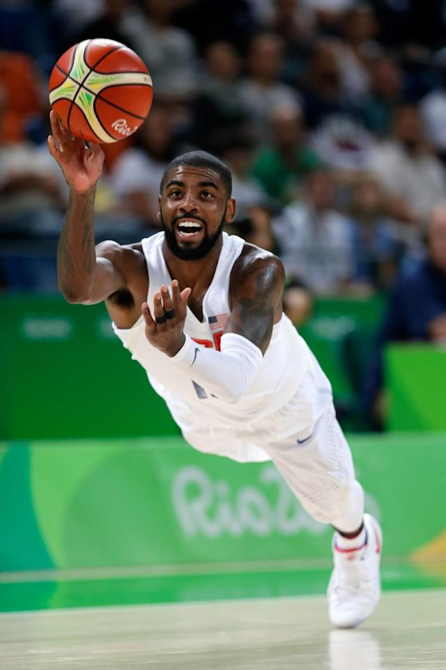<p>Kyrie Irving #10 of United States passes the ball to teammate Kevin Durant, not pictured, #5 before falling to the court during a Men's Preliminary Round Group A game between the United States and France Day 9 of the Rio 2016 Olympic Games at Carioca Arena 1 on August 14, 2016 in Rio de Janeiro, Brazil. (Photo by Jamie Squire/Getty Images) </p>