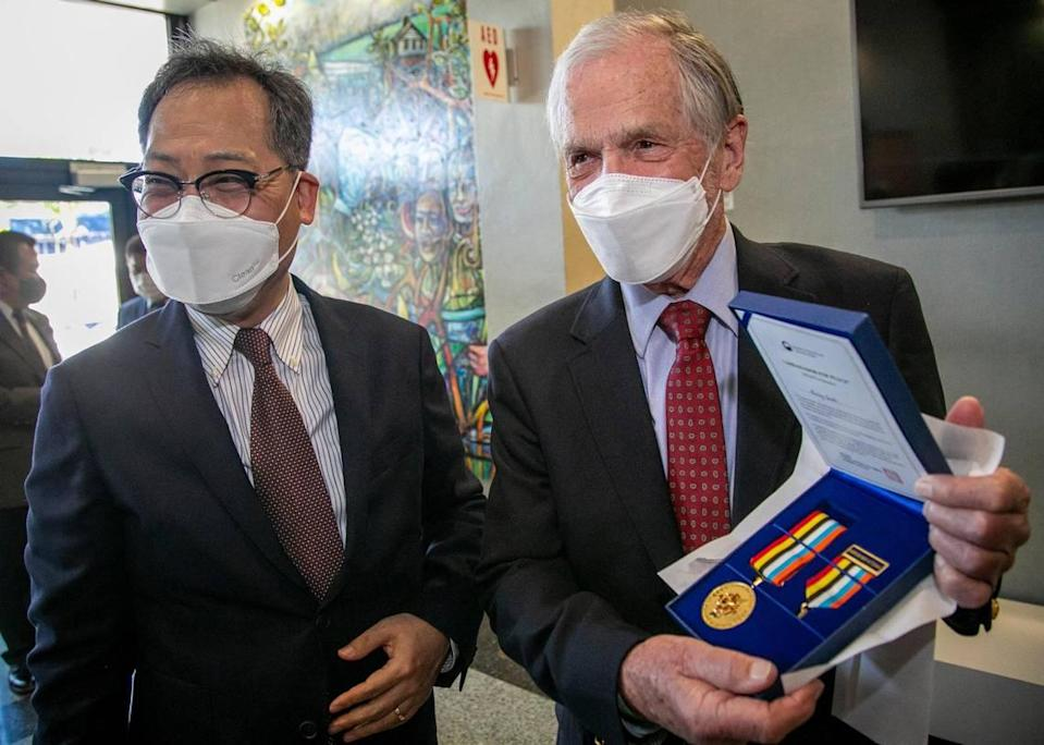 Burley Smith shows off the Ambassador for Peace medal awarded to him by the government of South Korea and presented to him by Korean Consul General Young-jun Kim, left, during a ceremony at Miami City Hall on Friday, January 22, 2021. The award commemorates the rescue of 14,000 Korean refugees by the SS Meredith Victory from the beaches of Hungnam 70 years ago. Burley Smith was a crew member aboard the Meredith Victory.