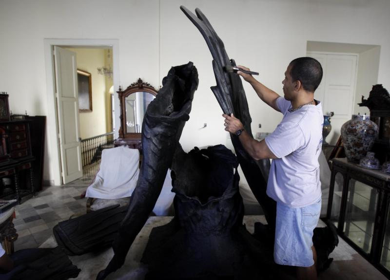 "In this Wednesday, Feb. 13, 2013 photo, a man works to restore the body of an eagle that was torn down from the Maine monument after the triumph of the revolution, at the History of the City Museum in Havana, Cuba. Following the doomed, U.S.-backed Bay of Pigs invasion, the more than 3-ton eagle was ripped from the USS Main monument during an anti-American protest and splintered into pieces. ""I have been the faithful custodian of the body,"" City Historian Eusebio Leal, told The Associated Press. (AP Photo/Franklin Reyes)"
