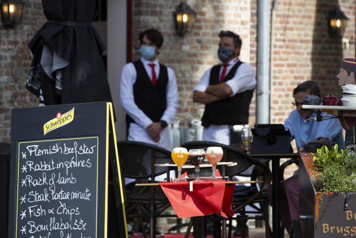 FILE - In this Monday, Aug. 24, 2020 file photo, two waiters, in protective face masks, wait on a nearly empty terrace at a restaurant in Bruges, Belgium. European Union leaders are meeting for a summit in Portugal on Friday, May 7 sending a signal they see the threat from COVID-19 on their continent as waning amid a quickening vaccine rollout. Their talks hope to repair some of the damage the coronavirus has caused in the bloc, in such areas as welfare and employment. (AP Photo/Virginia Mayo, File)