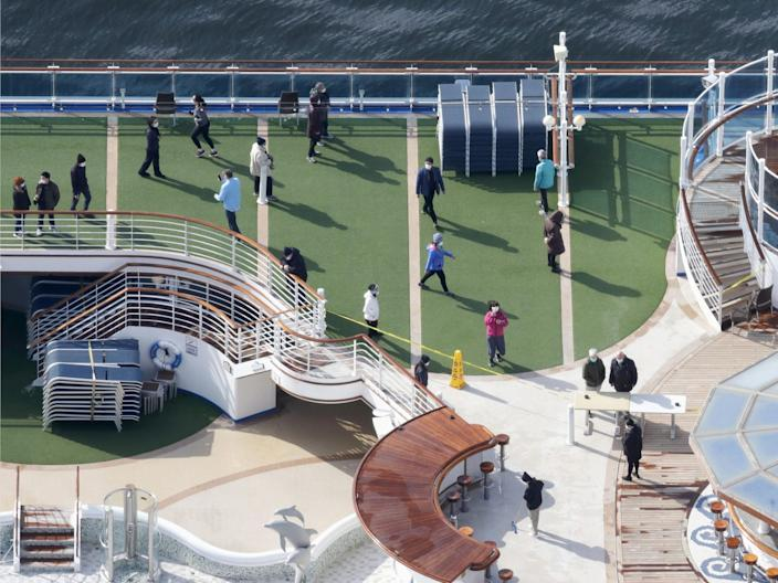 Passengers stroll on the deck of the Diamond Princess docked at the port of Yokohama on February 7, 2020.