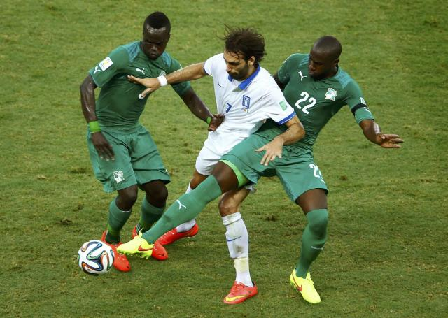 Ivory Coast's Tiote and Bamba challenge Greece's Samaras during their 2014 World Cup Group C soccer match at the Castelao arena in Fortaleza