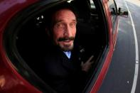 FILE PHOTO: Software pioneer John McAfee is escorted by immigration officers to the Guatemalan Airport in Guatemala City