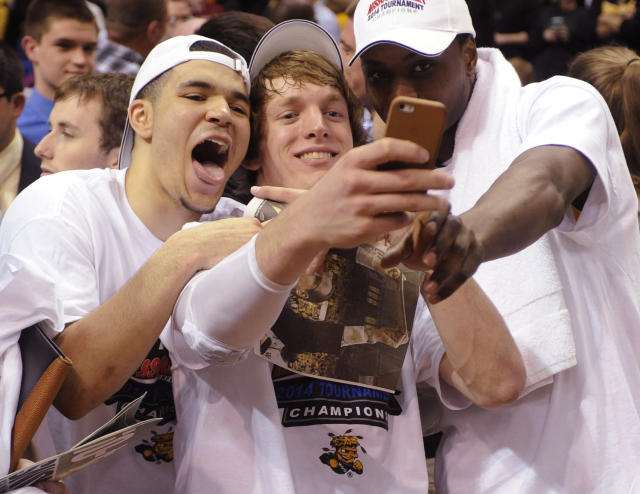 Wichita State's Ron Baker, center, takes a photo with Fred VanVleet, left, and Cleanthony Early, right, after their victory over Indiana State in an NCAA college basketball game in the championship of the Missouri Valley Conference men's tournament, Sunday, March 9, 2014, in St. Louis. (AP Photo/Bill Boyce)