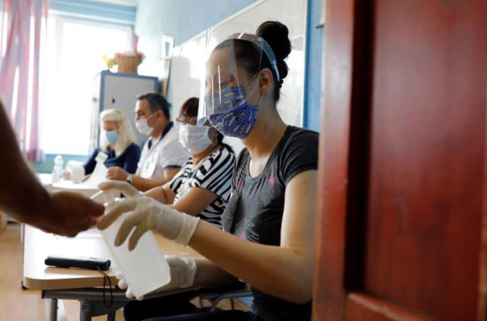 A member of an electoral commission wearing a face mask gives hand sanitiser to a voter at a polling station during the general election, in Strumica