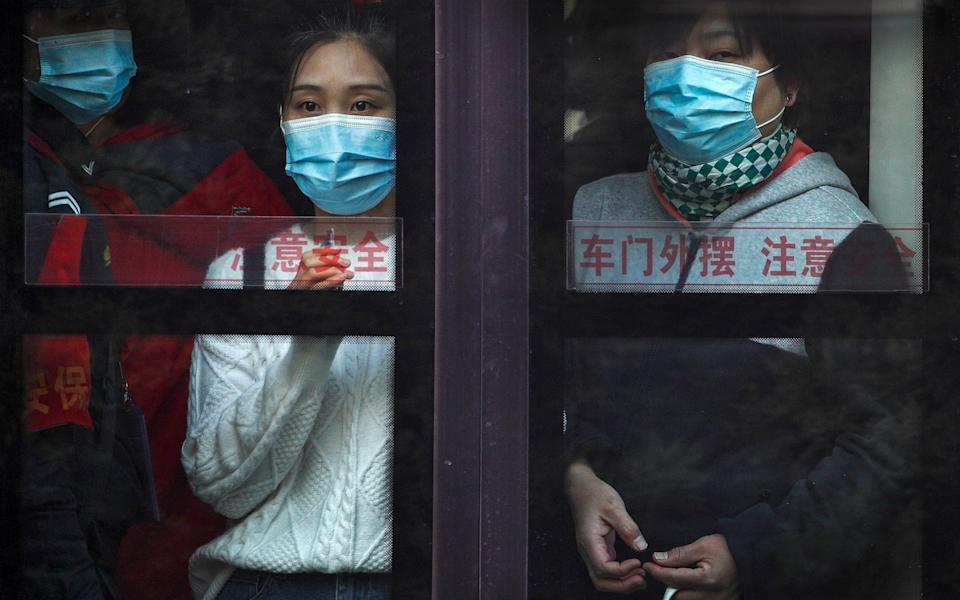 Commuters wearing face masks look out from a traveling bus during the morning rush hour in Beijing - AP
