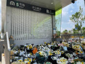 Bouquets of flowers are placed outside the entrance to a subway station in Zhengzhou in central China's Henan Province, Tuesday, July 27, 2021. Forecasters Monday said more heavy rain is expected in central China's flood-ravaged Henan province, where the death toll continues to rise after flash floods last week that killed dozens of people, including some in the inundated subway system in Zhengzhou. (AP Photo)