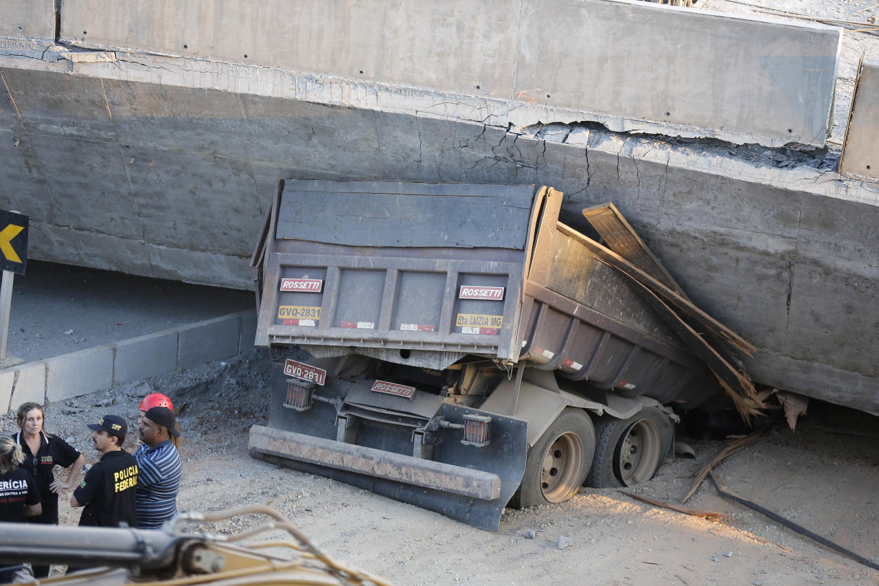 A truck is trapped underneath a collapsed bridge in Belo Horizonte, Brazil, Thursday, July 3, 2014. The overpass under construction collapsed Thursday in the Brazilian World Cup host city. The incident took place on a main avenue, the expansion of which was part of the World Cup infrastructure plan but, like most urban mobility projects related to the Cup, was not finished on time for the event. (AP Photo/Victor R. Caivano)