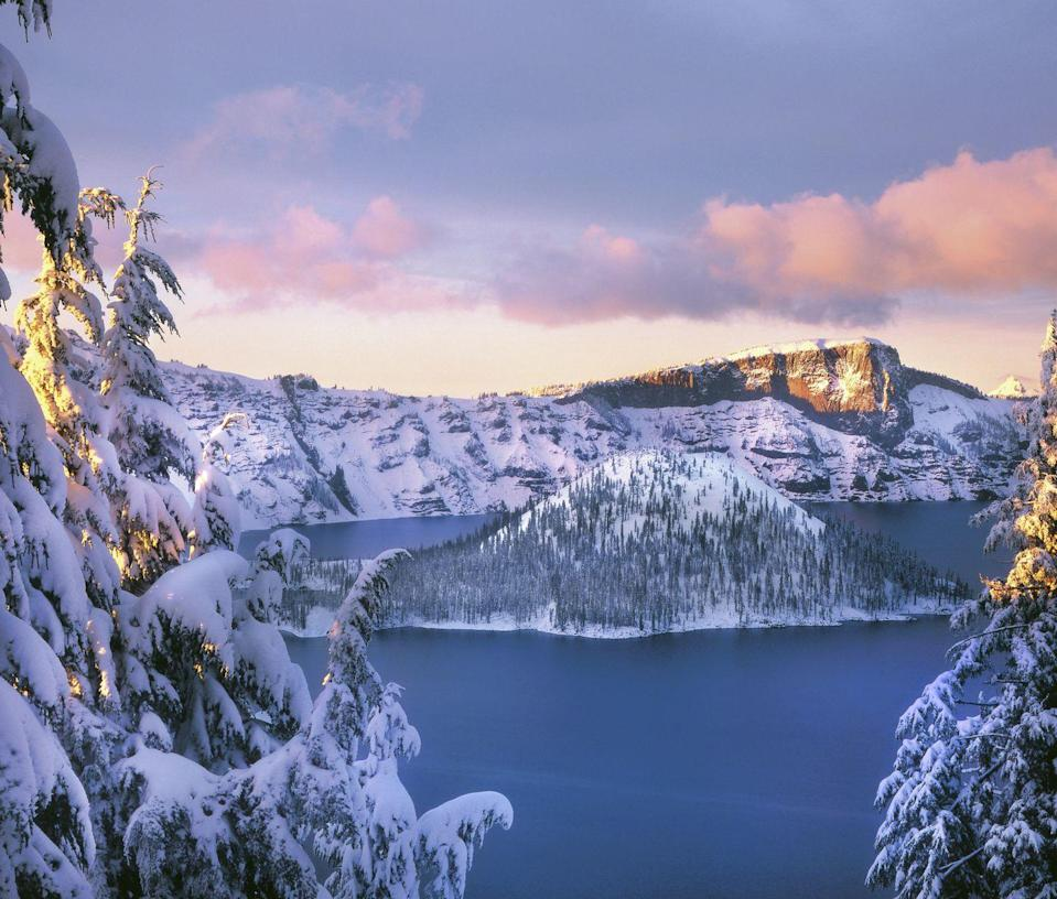 <p>The setting sun casts a pinkish-blue glow over the snow-covered mountains and trees overlooking Wizard Island. The snow only makes this always-magical scene even more special. </p>