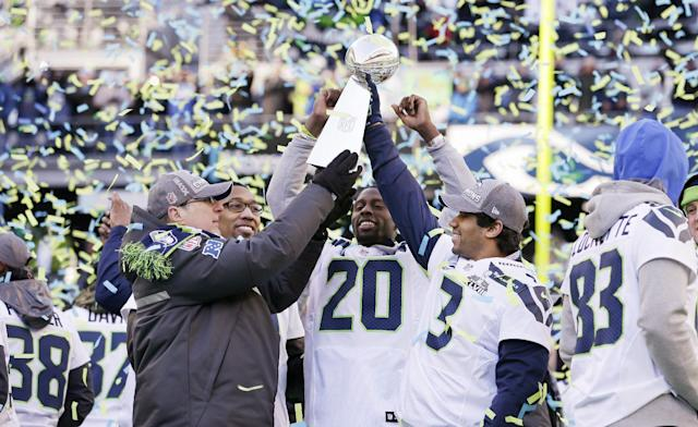 Seattle Seahawks team owner Paul Allen, left, holds up the Vince Lombardi Trophy with Russell Wilson (3) as Korey Toomer and Jeremy Lane (20) react at a rally following a parade for the NFL football Super Bowl XLVIII champions on Wednesday, Feb. 5, 2014, in Seattle. The Seahawks defeated the Denver Broncos on Sunday. (AP Photo/Elaine Thompson)
