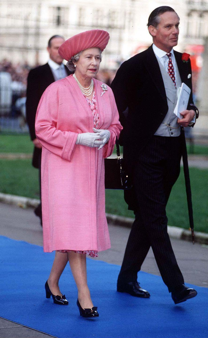 <p>A consummate monochrome pro, the Queen sported the bubblegum pink ensemble to the wedding of her nephew, Viscount Linley in 1993. </p>