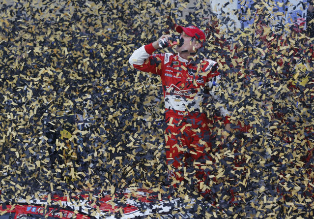 Driver Kevin Harvick celebrates in victory lane after winning the NASCAR Sprint Cup series auto race at Kansas Speedway in Kansas City, Kan., Sunday, Oct. 6, 2013. (AP Photo/Orlin Wagner)