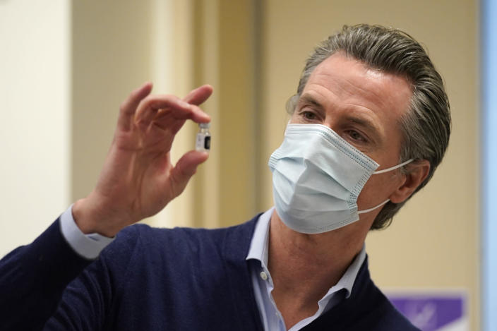 FILE - In this Dec. 14, 2020, file photo, California Gov. Gavin Newsom holds up a vial of the Pfizer-BioNTech COVID-19 vaccine at Kaiser Permanente Los Angeles Medical Center in Los Angeles. (AP Photo/Jae C. Hong, File)