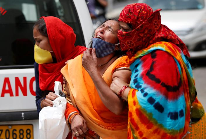 A woman is consoled after her husband died due to the coronavirus disease (COVID-19) outside a mortuary of a COVID-19 hospital in Ahmedabad, India, April 20, 2021. (Amit Dave/Reuters)