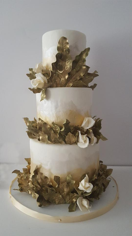 """<p>Metallics aren't just for your tablescape! """"I've been getting a lot of requests for metallics, namely a metallic ombré look,"""" says Deborah Lauren, founder of <a rel=""""nofollow"""" href=""""https://citysweets.com/?mbid=synd_yahoofood"""">City Sweets</a> in New York City. The combination of gold sugar leaves, soft gilded paint, and pearlescent white is subtly sparkling and so stunning.</p>"""