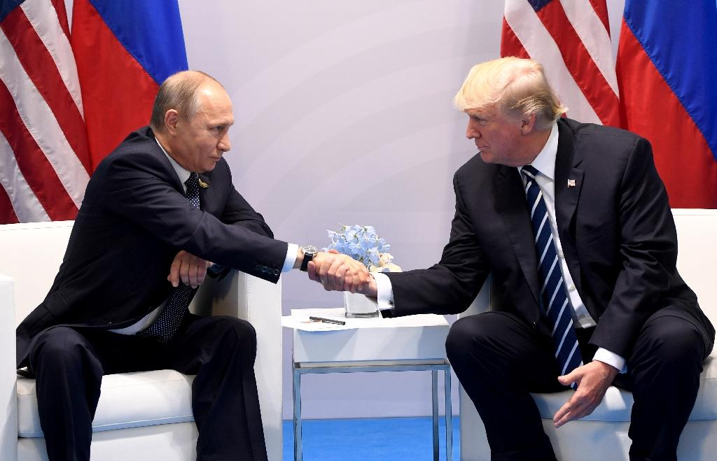<p>US President Donald Trump — shown here with Russia's President Vladimir Putin at the G20 summit in Germany in July — has long argued for better ties with Moscow (AFP Photo/SAUL LOEB) </p>