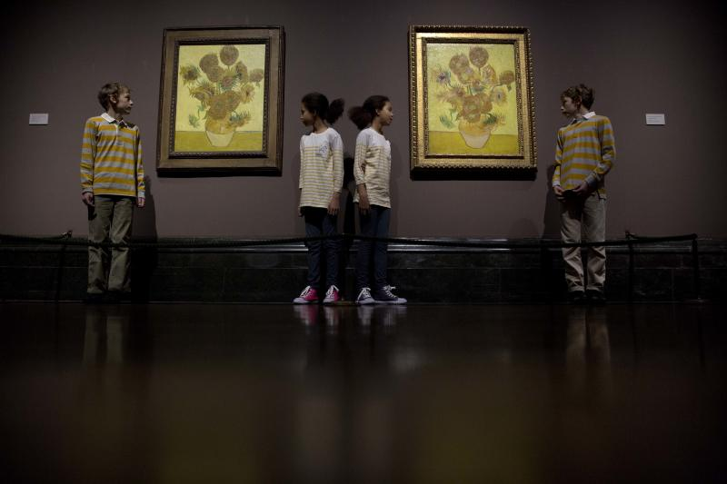 "Identical twins Ella, centre left, and Eva, centre right, aged 12, and twins Edgar, left, and Gabriel, aged 10, pose for photographers beside two versions of Dutch-born painter Vincent van Gogh's ""Sunflowers"", the left one from 1888 and the right one from 1889, during a photocall at the National Portrait Gallery in London, Friday, Jan. 24, 2014. The two paintings are being reunited in London for the first time in 65 years, with the 1889 version on loan from the Van Gogh Museum in Amsterdam. They will be displayed together until April 27. (AP Photo/Matt Dunham)"
