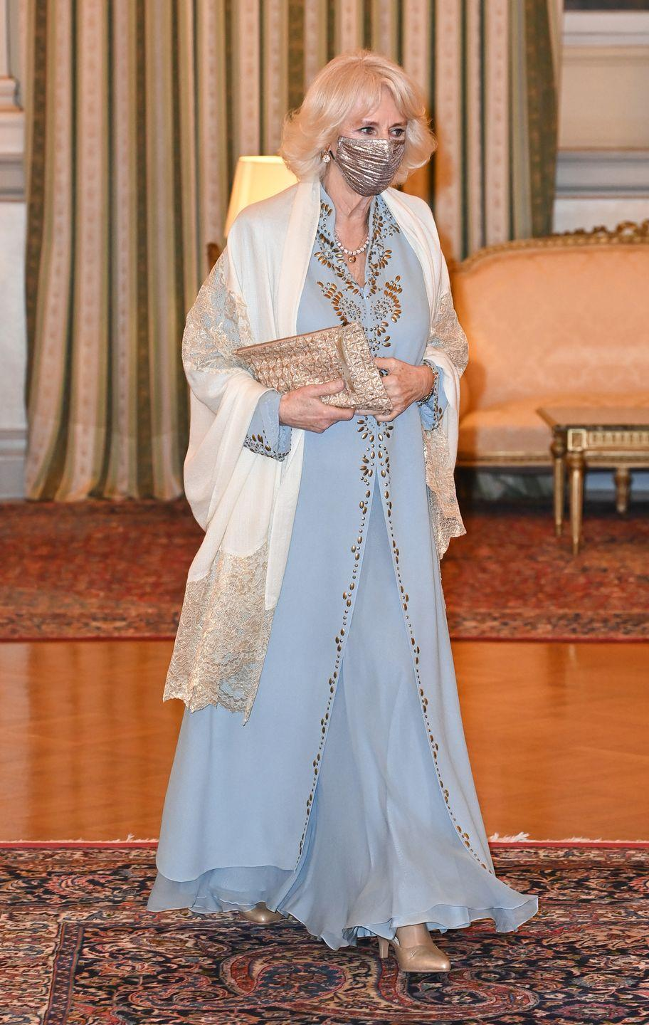 """<p>The Duchess of Cornwall stunned in a flowy light blue dress with gold detailing and a cream lace shawl for a reception on the first day of <a href=""""https://www.townandcountrymag.com/society/tradition/a35886831/prince-charles-camilla-royal-tour-greece-2021/"""" rel=""""nofollow noopener"""" target=""""_blank"""" data-ylk=""""slk:a trip to Athens"""" class=""""link rapid-noclick-resp"""">a trip to Athens</a> in <a href=""""https://www.townandcountrymag.com/society/tradition/g35936585/prince-charles-camilla-greece-photos-march-2021/"""" rel=""""nofollow noopener"""" target=""""_blank"""" data-ylk=""""slk:celebration of the 200th anniversary of Greek independence"""" class=""""link rapid-noclick-resp"""">celebration of the 200th anniversary of Greek independence</a>. She chose a matching shimmery gold clutch and a metallic gold face mask for the occasion, which was hosted by the President of Greece.</p>"""