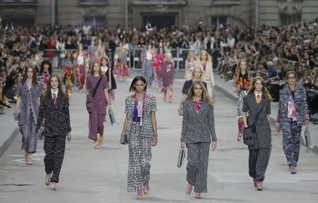 Models Josephine Le Tutour (2ndL) Binx Walton (3rdL) and Cara Delevingne (3rdR) present creations by German designer Karl Lagerfeld as part of his Spring/Summer 2015 women's ready-to-wear collection for French fashion house Chanel during Paris Fashion Week September 30, 2014. REUTERS/Gonzalo Fuentes